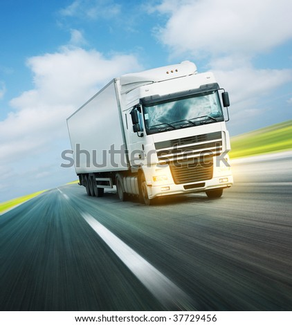 White truck on asphalt road under blue sky with clouds - stock photo