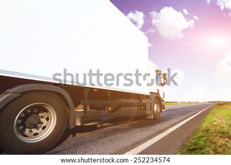 White truck on the asphalt rural road - stock photo