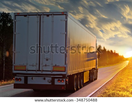 White truck on the rural road in evening. Sunset on the way. - stock photo