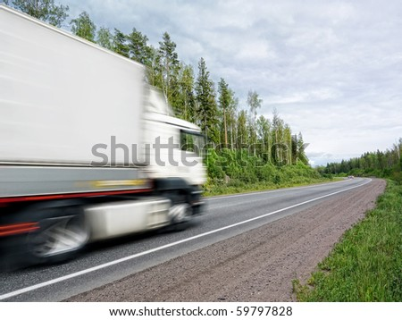 white truck speeding on country highway, blured in motion - stock photo