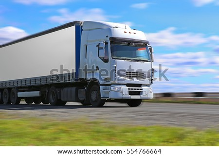 white truck transports freight on the country highway