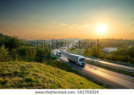 White trucks driving on the highway winding through forested landscape at sunset.