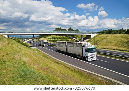 White trucks on asphalt highway goes under the concrete bridge in the countryside. View from above. Sunny day with blue sky and white clouds. - stock photo