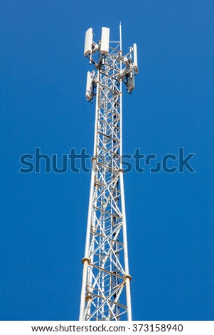 White truss structure tower of cell phone antenna with blue sky. - stock photo