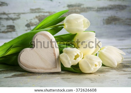 white tulips and a heart of wood on a vintage gray wooden background, love concept, closeup with selected focus and narrow depth of field - stock photo