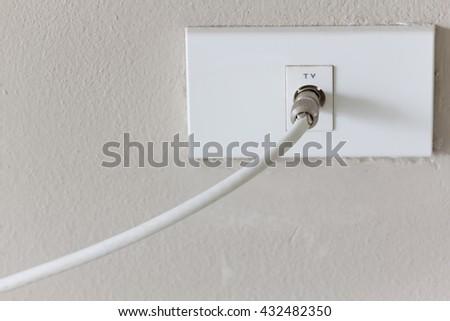 White tv plug on white wall, plug copy space, plug socket, plug electric, plug outlet, plug switch, plug backdrop, plug background. - stock photo