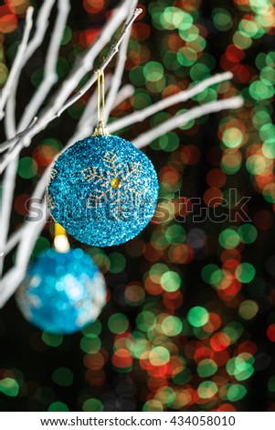 White twigs with Christmas tree baubles in front of a green red background - stock photo