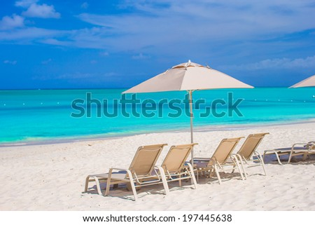 White umbrella and sunbeds at tropical beach