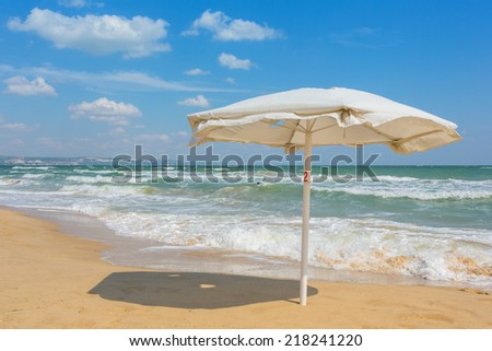 White umbrella on the beach with cloudy blue sky in background - stock photo