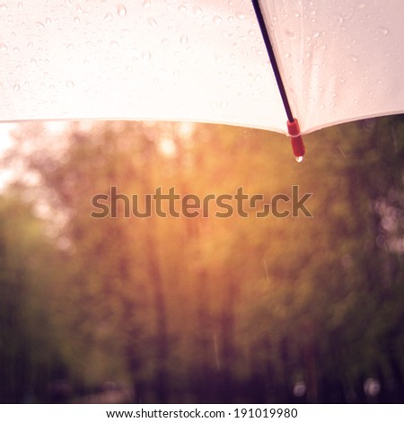 White umbrella with a drop of rain - instagram effect. Rainy day photo with retro filter. - stock photo