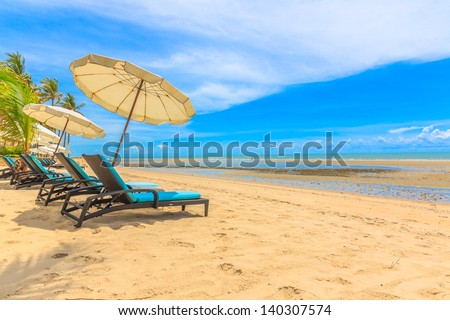 white umbrellas and chair at the beach with blue sky and white cloud, hua hin, thailand - stock photo