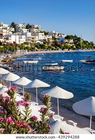 White Umbrellas and sunbeds near lagoon with boats on the beach in Bodrum, Turkey - stock photo