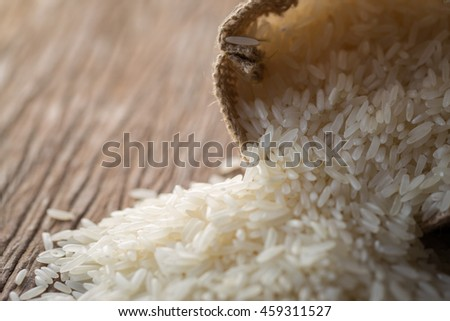White uncooked rice in small burlap sack on wooden background