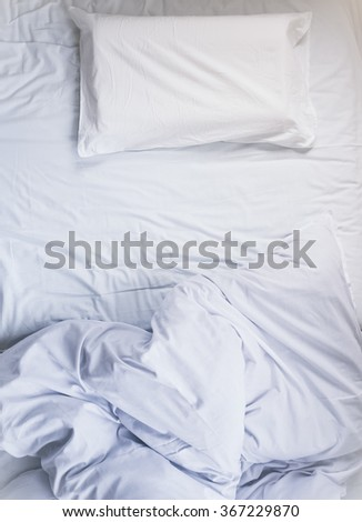 White unmade Bed mattress Duvet with pillow and blanket Top view - stock photo