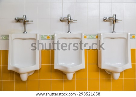 white urinals in men's restroom public toilets - stock photo