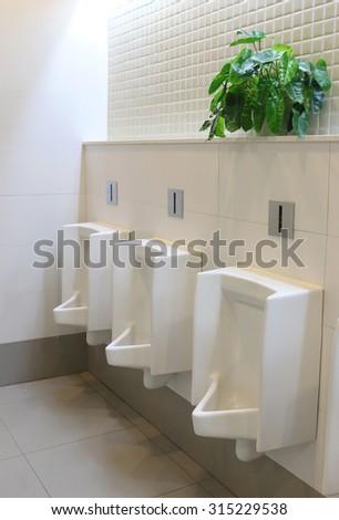 white urinals in public men's bathroom. - stock photo