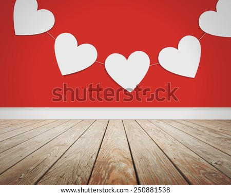 White Valentine's Day hearts are hanging from a string on a red background with a wooden floor for a photography backdrop or love concept. - stock photo