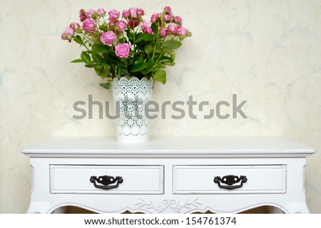 White vase full of pink roses on a counter - stock photo