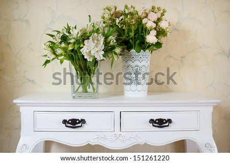 White vase full of white flowers on a counter - stock photo