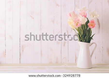 White vase with delicate shades armful of tulips on a wooden background - stock photo
