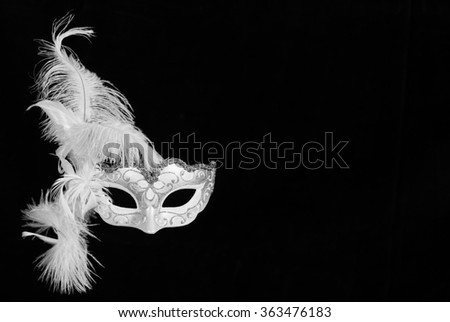 white Venetian mask carnival with feathers on black background with free space for text.