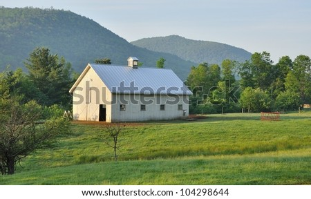 White Vermont barn in a green field in morning light - stock photo