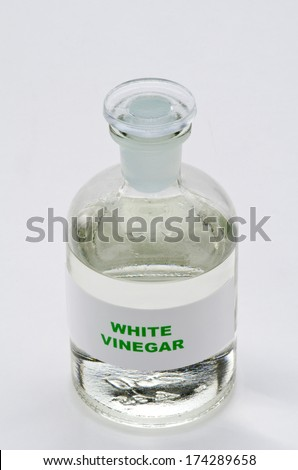 White vinegar in a glass bottle. White background. - stock photo