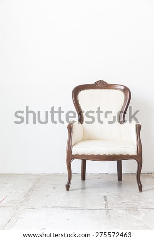 White vintage armchair on white wall.
