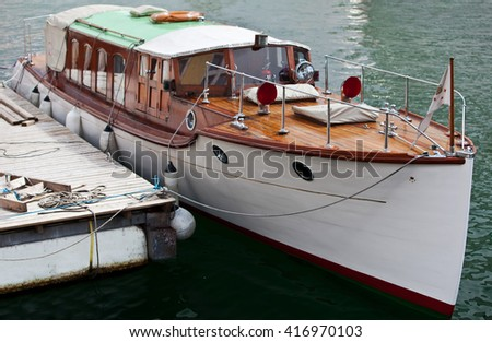 White vintage boat with wooden deck at pier