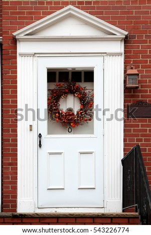White vintage entry door in New York decorated with wreath. USA.