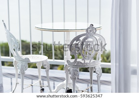 white vintage wrought iron gardening furniture set of empty round table and two elegant chairs