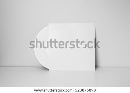 white vinyl record in white paper case put on table and leaning against a wall