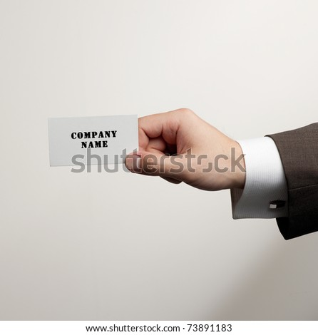 White visit card in hand isolated in studio - stock photo