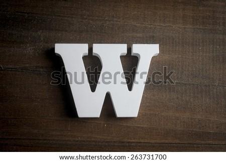 "White ""W"" letter on dark wooden background - stock photo"