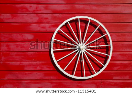 White wagon wheel is used as an ornament for a red barn.