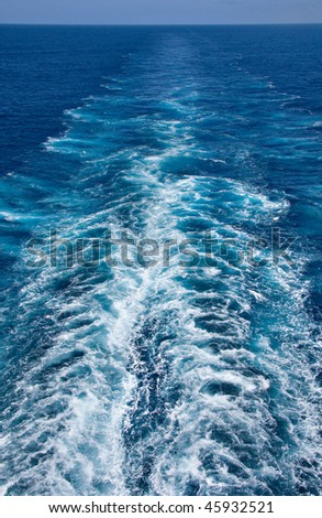 white wake in bright blue ocean left by a cruise liner