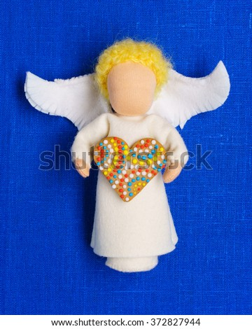 White waldorf doll angel, holding gingerbread heart, lying on a deep blue linen fabric background - stock photo