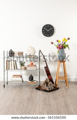 white wall black chair with vase of flower and guitar - stock photo