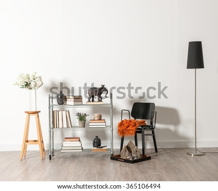 white wall black chair with vase of flower and trinket - stock photo