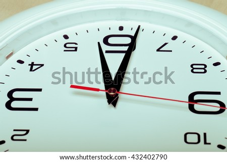 White wall clock with black arrows. Selective focus. Shallow depth of field. Toned.