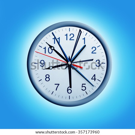 White wall clock with many hands over blue - stock photo