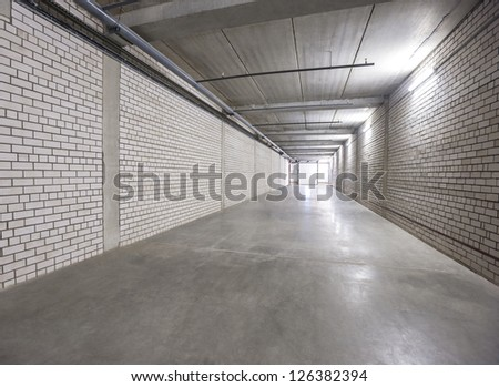 white wall  corridor to exit illuminated by fluorescent lamp - stock photo