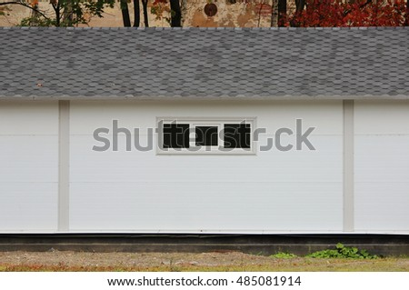 White wall texture house, dark windows, flexible grey tiles on the background of multi-colored leaves of autumn forest