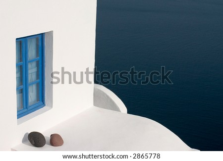 white wall with blu window and stones