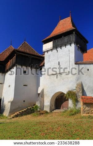 White walls surrounding fortified church on UNESCO world heritage list in Viscri village, Transylvania, Romania - stock photo