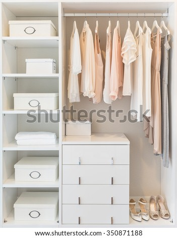 white wardrobe on wooden floor with dress hanging on rail - stock photo