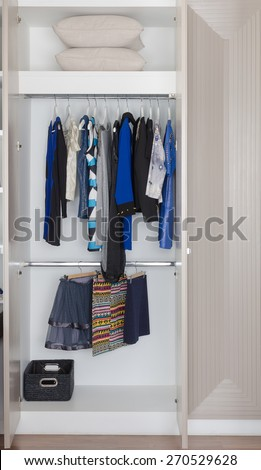 white wardrobe with clothes hanging at home - stock photo