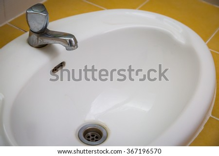 White wash sink in a bathroom with open the water background