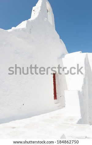 White washed wall of a Greek house on Mykonos with a window with red painted shutters against a clear blue sunny sky - stock photo