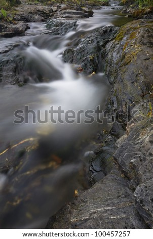 White water and rocks of small, fast moving stream. Cornwall, UK.